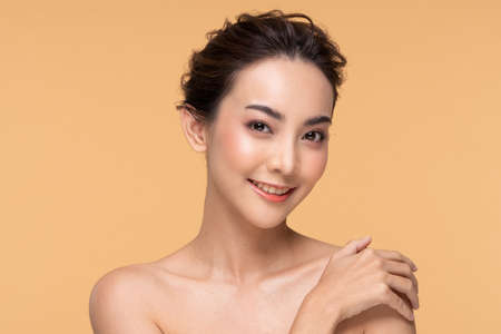 Beautiful Young Asian Woman Looking While Touching Shoulder feeling so happy and cheerful with healthy Clean and Fresh skin,isolated on Beige background,Beauty Cosmetology Concept