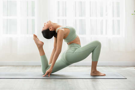 Side view of Asian woman wearing green sportwear doing Yoga exercise,Yoga One Legged King Pigeon pose or Eka Pada Rajakapotasana,Calm of healthy young woman breathing and meditation with yoga at home