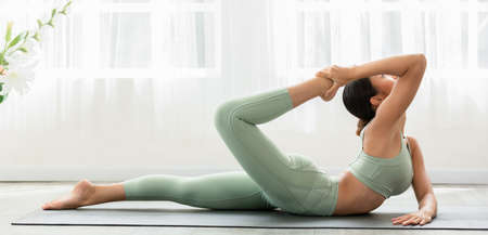Side view of Asian woman wearing green sportwear doing Yoga exercise.Yoga bow or dhanurasana pose.Calm of healthy young woman breathing and meditation with yoga at home.Exercise for wellness life