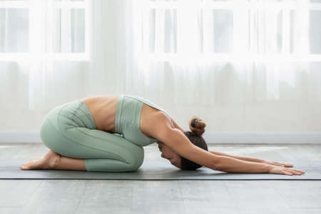 Side view of Asian woman wearing green sportwear doing Yoga exercise,Yoga Child's pose or Balasana,Calm of healthy young woman breathing and meditation with yoga at home,Exercise for wellness life