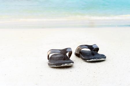 Sandals on the sandy beach summer concept