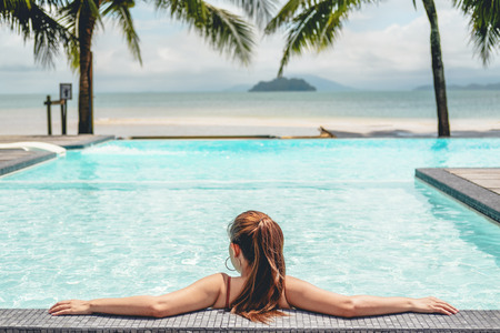 Carefree woman relaxation in swimming pool summer Holiday concept 版權商用圖片