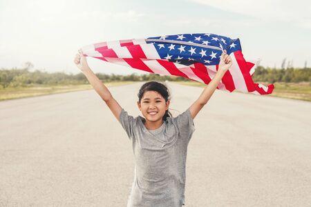 Feliz niña asiática con bandera estadounidense Estados Unidos celebra el 4 de julio