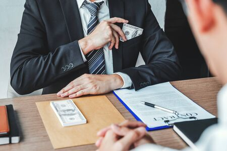 Corruption and Bribery,Businessman giving dollar bills corruption bribery to business manager to deal contract Foto de archivo