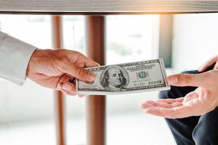 Corruption and Bribery,Businessman giving dollar bills corruption bribery to business manager to deal contract Banco de Imagens