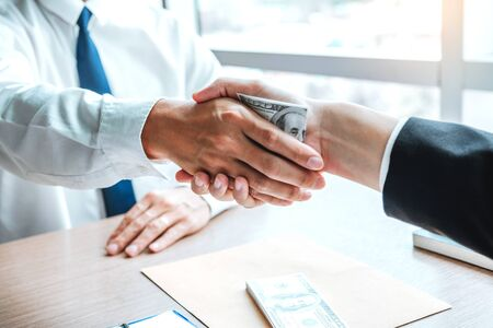 Corruption and Bribery ,Businessman shaking hands giving dollar bills corruption bribery to business manager to deal contract