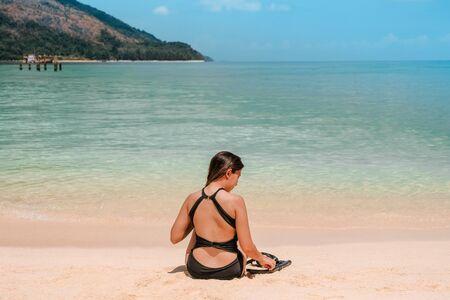Summer Asian women relaxing on the sandy beach before Snorkel