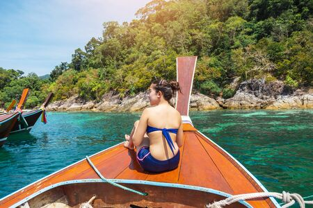 Asian women relaxing in summer holiday tropical sea with long-tail boat in thailand
