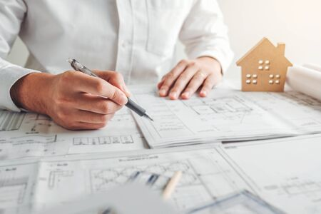 Engineer drawing graphic planning working with architectural project on workplace office.