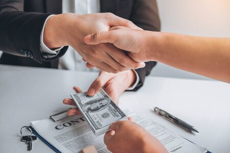 Sale Agent handshake with woman customer and sign agreement documents for realty purchase after successful loan contract .