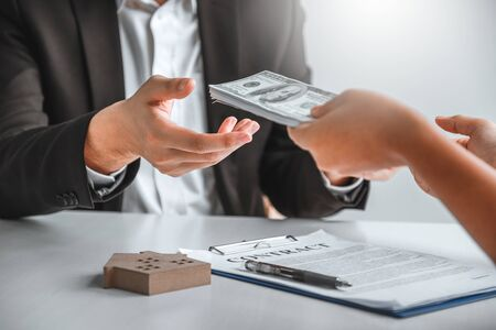 Woman customer sign agreement buying home ,salesman receive money after good deal after successful loan contract . Banco de Imagens