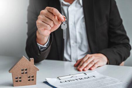 Verkaufsagent, der der Kundin Hausschlüssel übergibt und Vertragsdokumente für den Immobilienkauf unterschreibt.