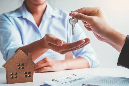 Sale Agent giving house keys to woman customer and sign agreement documents for realty purchase.