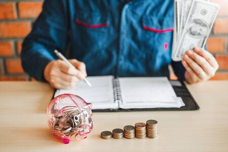 Man calculator Accounting Calculating with Piggy bank money stack step growing saving money Banco de Imagens - 128696514