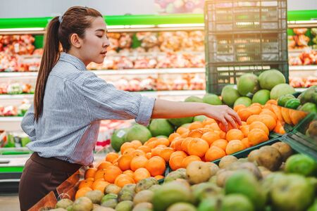 Asian women shopping Healthy food vegetables and fruits in supermarket