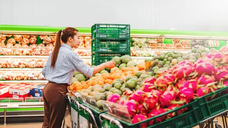 Asian women shopping Healthy food vegetables and fruits in supermarket Banco de Imagens - 130738538