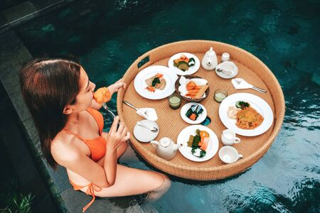 Floating breakfast in infinity pool on paradise swimming pool, morning in the tropical resort Bali, Indonesia