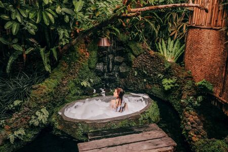 Woman relaxing in outdoor bath with tropical jungle  luxury spa hotel, lifestyle