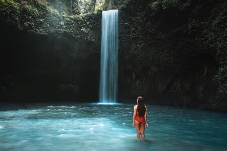 Traveling young woman with tropical rainforest in Bali enjoying life at beautiful Tibumana waterfall.