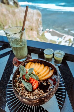 Granola fruit yogurt for healthy breakfast with sea view