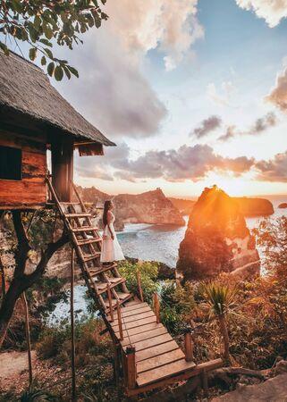 Travel woman looking sunrise view Tree House with Diamond  beach, Nusa Penida island Bali, Indonesia Banco de Imagens - 130737423