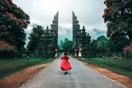 Traveler Woman Running at the Gates Hindu temple Bali, Indonesia Banco de Imagens - 130736707