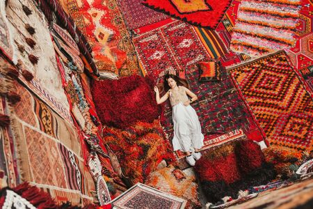 Happy travel woman with amazing colorful carpets in Local carpet shop, Goreme. Cappadocia Turkey Banco de Imagens - 130736925