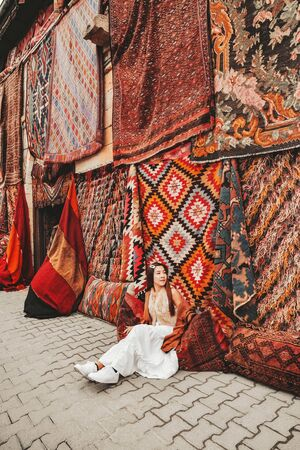Happy travel woman with amazing colorful carpets in Local carpet shop, Goreme. Cappadocia Turkey