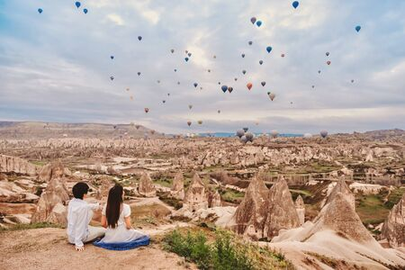 Asian couple watching colorful hot air balloons flying over the valley at Cappadocia, Turkey This Romantic time of love Banco de Imagens