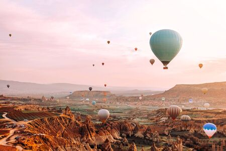 Colorful hot air balloons flying over the valley at Cappadocia sunrise time popular travel destination in Turkey Banco de Imagens - 130734397