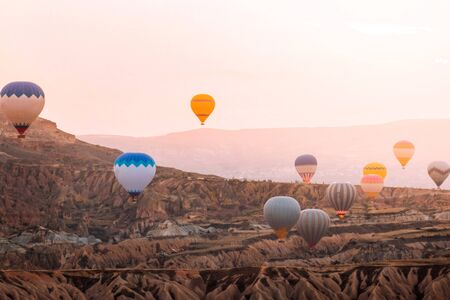 Colorful hot air balloons flying over the valley at Cappadocia sunrise time popular travel destination in Turkey Banco de Imagens - 130734399