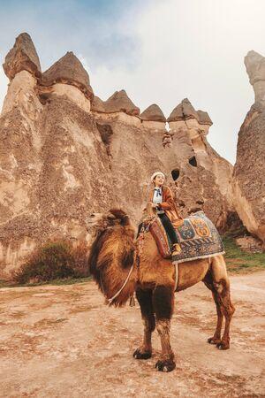 Traveler woman riding camel at Goreme fairy chimneys, Cappadocia. Nevsehir Province. Turkey. Banco de Imagens - 130734406
