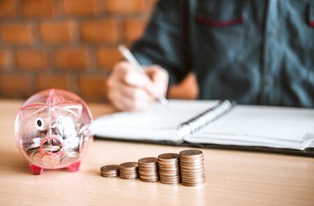 Man calculator Accounting Calculating with Piggy bank money stack step growing saving money Banco de Imagens - 130733686