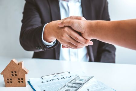Sale Agent handshake with woman customer and sign agreement documents for realty purchase after successful loan contract Banco de Imagens