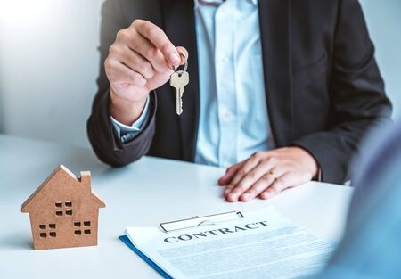 Sale Agent giving house keys to woman customer and sign agreement documents for realty purchase. Banco de Imagens - 130731449