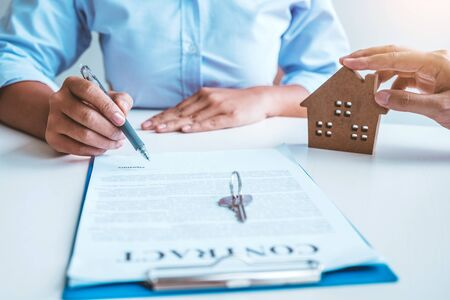 Sale Agent giving house keys to woman customer and sign agreement documents for realty purchase. Banco de Imagens - 130731467