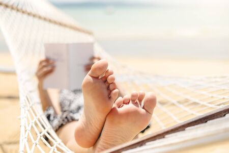 Woman reading a book on hammock beach in free time summer holiday Banco de Imagens - 130731474