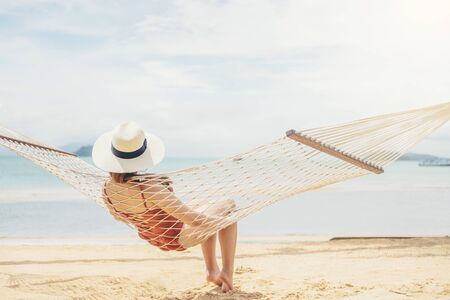 Woman relax on hammock beach in free time summer holiday
