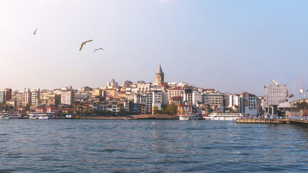 View of Istanbul cityscape Galata Tower with floating tourist boats in Bosphorus, Istanbul Turkey