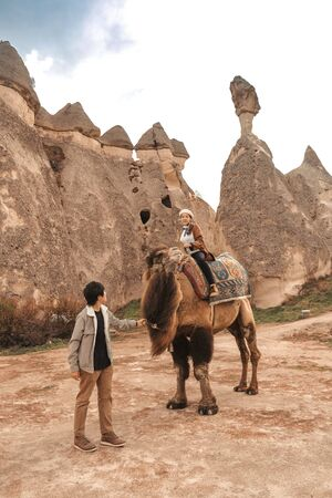 Traveler couple with camel at Goreme fairy chimneys , Cappadocia. Nevsehir Province. Turkey.