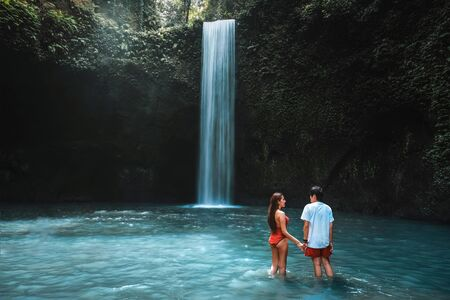Traveling young couple with tropical rainforest in Bali enjoying life at beautiful Tibumana waterfall.