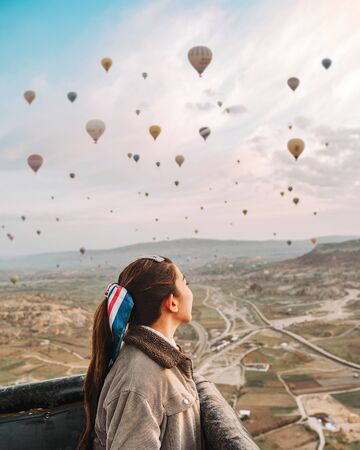 Asian woman watching colorful hot air balloons flying over the valley at Cappadocia, Turkey This Romantic time Banco de Imagens