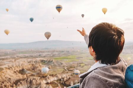 Asian man watching colorful hot air balloons flying over the valley at Cappadocia, Turkey This Romantic time Banco de Imagens