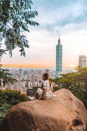 Traveler women and sunset with view of skyline of Taipei cityscape Taipei 101 building of Taipei financial city ,Taiwan stock