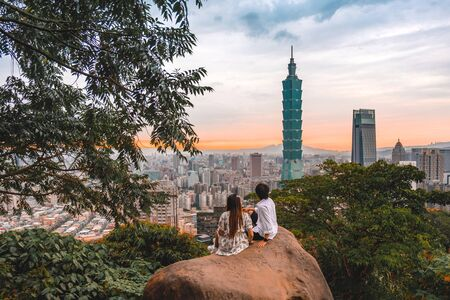 Traveler couple and sunset with view of skyline of Taipei cityscape Taipei 101 building of Taipei financial city ,Taiwan stock Banco de Imagens