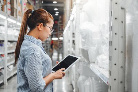 Asian woman worker working with digital tablet checking boxes Logistic import and export supplies packages in Warehouse , Logistics concept Banco de Imagens