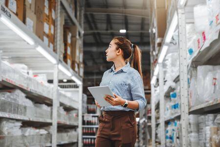Aziatische vrouwelijke werknemer die werkt met digitale tablet die dozen controleert Logistieke import- en exportleveringspakketten in magazijn, logistiek concept Stockfoto