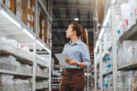 Trabajadora asiática que trabaja con casillas de verificación de tableta digital Paquetes de suministros de importación y exportación logística en almacén, concepto de logística Foto de archivo