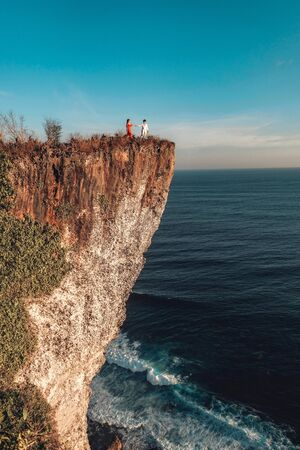 Couple Adventure and looking view on the karang boma cliff at Uluwatu Bali in Indonesia Banco de Imagens