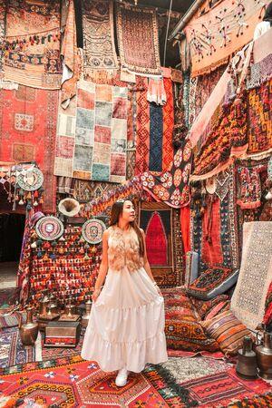 Happy travel woman with amazing colorful carpets in Local carpet shop ,Goreme. Cappadocia Turkey Banco de Imagens